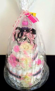 Final look :) all wrapped up with a bow! Baby Girl pink & black damask diaper cake.  Custom made by Sweet Moments.  Like facbook fan page for more info