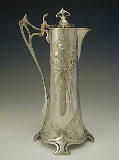 WMF Claret jug, 1906.  Polished pewter 30cm tall Germany Distinctly Art Nouveau with twirling whiplash patterns and organic motifs. True to Art Nouveau in Germany and Austria, the design is very symmetrical in contrast to the asymmetry of designs elsewhere.