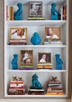 not wild about the blue sculptures but i love the idea of arranging frames on top of stacks of books!