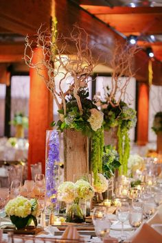 tall and dramatic wedding centerpieces with branches and hydrangea in wooden column vases