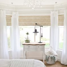 Jute-like rollers shades and serene master bedroom inspiration.