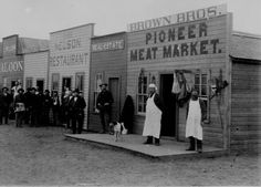 Broadway Street, Round Pond, Oklahoma territory. Shopkeepers and customers pose in doorways. 1894.
