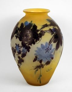 A large yellow glass vase depicting intense and light blue flower decorations. Measures 17 1/4 inche in height, made in France, circa 1905