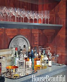 Inspired by a gentleman's smoking lounge, the bar in this New York apartment designed by David Rockwell, built by C. Stasky, is clad in Maya Romanoff's True Metals Coffers. William Yeoward crystal. Ebony Pearl Silestone counter.   - HouseBeautiful.com