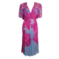 Hanae Mori floral silk wrap dress | Japan, circa 1980's | Silk party dress features a bold, photographic floral placement print. The wrap style bodice is printed with electric blue, lavender and white flowers, and is edged in hot pink satin trim. Sheer peekaboo flutter sleeves are gathered from the shoulder. Back bodice and skirt are printed with a vibrant cherry blossom style tree motif. Shoulders are lightly padded, waist is elasticized