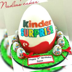 maybe i could bake the bottom half in a big mixing bowl, the top half in a small mixing bowl and round cake/s in the middle and carve them until they are flush write happy birthday instead of kinder surprise - happy in red with a black H and birthday in the same colours as surprise then maybe alexus in blue? a number 3 somewhere?