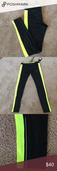 Nike tight fit essential Nike tight fit essential running pants, black with yellow stripes, zippers from ankle to calves on back side, small zip pocket on top of butt, elastic drawstring waist, size L NWT Nike Pants Track Pants & Joggers