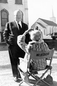 "Tippi Hedren talking to director Alfred Hitchcock while sitting on his chair on the set of ""THE BIRDS"" (1963)."