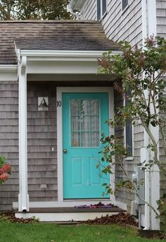 Turquoise door with grey cedar shingles. Cute! A bright green door would look nice too!