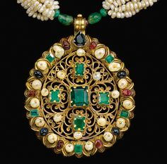 [DETAIL] A GEM-SET AND SEED PEARL GOLD NECKLACE (TAZRA), MOROCCO, 18TH CENTURY composed of three hanging sections on a seed pearl necklace, separated by two cylindrical elements with enamelled floral motifs, the hanging roundels of gold-filigreework set with gems, with tiger's stone inset clasp