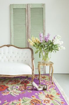 We love the idea of a crisp white couch against a gorgeous floral carpet. This combo works great on an indoor or outdoor patio.