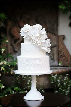 All white tiered cake with massive floral cluster on top