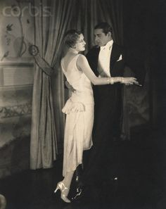 Model Edwina St. Clair, wearing a sleeveless, fitted, white chiffon dress with fluttering ends by Louiseboulanger, and diamond cuff bracelets by Black, Starr and Frost, and dancing with a man in a white tie and a black tuxedo.  ca. 1928  Edward Steichen