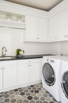 Equipped with a white front loading washer and dryer placed on gray hex floor tiles beneath white shaker cabinets, this well designed gray and white laundry room features a gray ceiling and white shaker cabinets contrasted with a black quartz countertop fitted with a curved white porcelain sink.