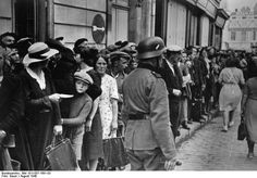 Occupation of France, August 1940: Refugees from Alsace gather outside German HQ in the city of Cognac.