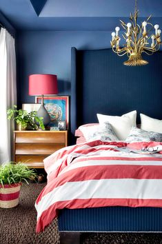 Dark blue bedroom with red lamp and bed sheets