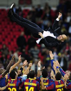 Pep Guardiola is thrown in the air after Barcelona wins the Champions League final soccer match against Manchester United at Wembley Stadium, 2011.