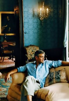George Clooney pensive and well coordinated  ( in color and charm only) with his old world interiors at his villa in Laglio, Italy