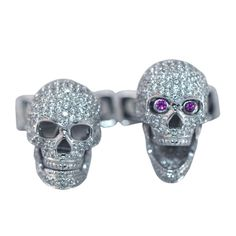 HANCOCKS White gold & diamond skull cufflinks with ruby eyes  England  Contemporary  Pair of 18ct white gold cufflinks designed as a skull and crossbone pavé-set in diamonds with ruby eyes. The jaw opens and closes to reveal or conceal the ruby eyes. Made by Deakin & Francis for Hancocks.