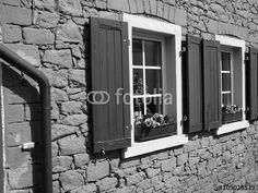 Sprossenfenster mit schönen Holzfensterläden in schwarzweiß und mit Bruchsteinfassade in Großauheim bei Hanau am Main in Hessen