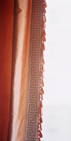 Salmon colored silk draperies are enhanced by sky blue Greek key tape trim and coral wooden bobble fringe. - Traditional Home ® / Photo: Patrick Cline / Design: Sara Gilbane