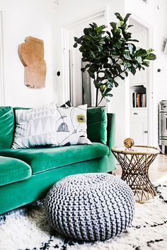 Eclectic living space with bright emerald couch and a neutral pouf
