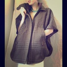 Topshop Houndstooth Pancho Fall Winter Coat Vest Excellent condition. No stains, holes or tears. Zipper works. This comes from a smoke free home. There are buttons on the sides. Plaid Scottish outlander look and feel. Great with leather riding boots. Made in Romania. Exterior fabric is 47% Acrylic, 23% wool, 21 % wool, 6% nylon, 3% cotton. Topshop Jackets & Coats Vests