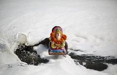 A devotee carries a statue of the Hindu god Ganesh, the deity of prosperity, in the polluted waters of the river Yamuna on the final day of the Ganesh Chaturthi festival, in New Delhi, India
