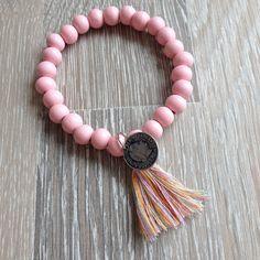 Armband van 8mm zacht roze hout met meerkleurig kwastje en een metalen dubbeltje. Van JuudsBoetiek, te bestellen op www.juudsboetiek.nl.