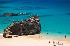 Jump off the rocks at Waimea Bay, Oahu, Hawaii