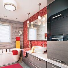 La configuration initiale est restée quasiment identique, à ceci près quela baignoire et la toilette ont échangé leur place. Plus imposant que celuid'origine, le nouveau mobilier en mélamine deux tons se présente commela pièce maîtresse de la salle de bain. Bordé d'une bande en inox, soncomptoir en céramique d'un blanc pur tranche avec la chaleur du dosseretde mosaïque rouge rubis et de la céramique murale à effet bois.