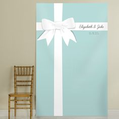Like a large gift-wrapped package, this 4 ft. by 7 ft. backdrop features a white ribbon and bow design over a teal-blue background personalized with the bride and groom's first name and wedding date.
