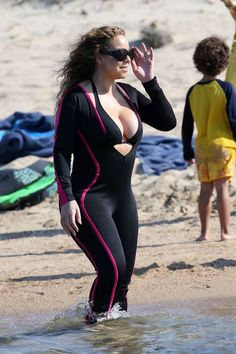Mariah Carey in a black bikini top and an unzipped wetsuit on the beach in Sardinia