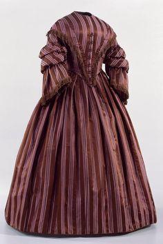 KLEID (DAMEN) LM-36203 Kleid (Damen). Vorne und hinten sogen. Schneppentaille. Abfallende Schultern, ausladende Ärmel. Seide, gewebt, gefüttert. Um 1855. Masse: Höhe 151 cm. (LM-36203)