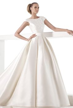 Brides: Pronovias. Bodice in mikado silk with bateau neckline, gemstone embroidery and floral motifs. Short sleeves and deep rounded back. Wide princess skirt in mikado silk. Mikado silk sash and pleats from waist.