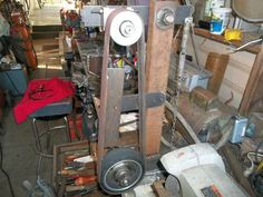 Belt Grinder by gtermini -- Homemade belt grinder constructed from DOM tubing, steel plate, bushings, aluminum and rubber wheels, and a 1.5 hp motor.  http://www.homemadetools.net/homemade-belt-grinder-40