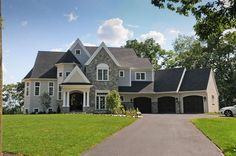 stone and stucco with carriage house garage doors and white windows..