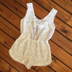 """Sweet Little Lace Romper Ready for summer?! This little ivory lace romper is the cutest swim cover up! Purchased for my honeymoon but never wore, so it is brand new with tags in PERFECT condition. Elastic waist accommodates a wide range of sizes. Measures 14"""" across the elastic waist band when laid flat and approximately 28"""" from shoulder to hem as measured in photo 4. From a smoke-free, pet-free home. Swim Coverups"""