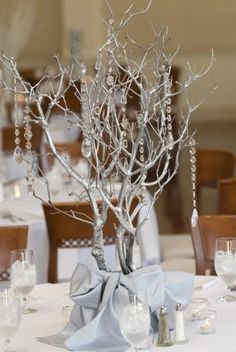 Centerpiece features silver branches with hanging rhinestones...