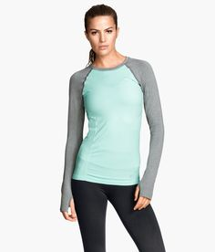 Fitted mint green sports top with functional fabric, cuff thumbholes, and long sleeves in contrasting gray. | H&M Sport