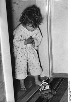 Old picture of a child who finds presents in her shoe from Sinterklaas (a traditional dutch winter holiday figure like santa)