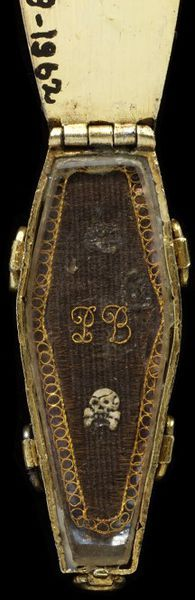 "1703 British Pendant at the Victoria and Albert Museum, London - From the curators' comments: ""This intricate jewel is in the form of a coffin which opens to reveal a panel of woven hair, initials, and an enamelled skull. It is an unflinching reminder of man's mortality while specifically commemorating the death of a particular individual, the now unknown PB. Such graphic imagery was a widely accepted part of the rituals surrounding death in the years around 1700."""