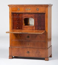 A Biedermeier secretaire à abattant in mahogany with pine secondary, having a rectangular top above a dovetailed frieze drawer centered by a floral, gilt-metal mount, over a hinged fall front opening to a fitted interior with six drawers, all surrounding a Neoclassical insert with a mirrored back and park scenes on the walls, the floor inscribed J.J. Egerin. / 1832.