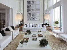 Almost all white! A clean, comfortable looking room. Fabulous, tall wall flanked by huge chandeliers. Small accents of black & green.
