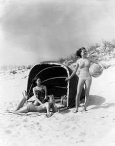 Photo : Three Women On Beach Two Are Under Canvas Sun Wind Screen With Fringe Other Is Standing Holding A Ball.