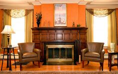 Wood burning fireplace with wooden mantle in living room with Venetian plaster walls.