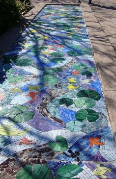 Garden Art - Mosaic designed by artist Heather Anderson.  We've all seen mosaic stepping stones that make a pathway sparkle, but there's a world of other ways to use mosaics in the garden.