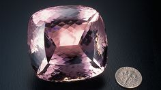 This kunzite from Minas Gerais, Brazil, weighs 648.10 carats. It's shown next to a dime to demonstrate scale. - Robert Weldon, courtesy M. Meienhalder