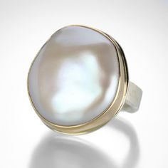 This Jamie Joseph ring is loaded with gorgeous luster.  The asymmetrical cultured pearl is set in a 14k yellow gold bezel, on a sterling silver 'Live Edge' band that echos the organic shape of the pearl.  We love the baroque drama that this ring brings! @QUADRUM