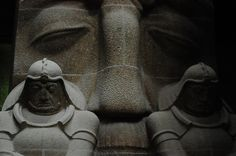 two stone warriros and a giant face watching over the crypt in the Völkerschlachtdenkmal in Leipzig